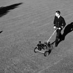 Un homme en costume qui tond la pelouse en 1943